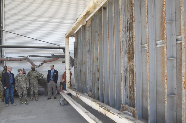 Wade McMath (far left), MARID program coordinator, talks to Brig. Gen. Heidi J. Hoyle, commanding general, Joint Munitions Command, about shipping container repairs during her visit to McAlester Army Ammunition Plant, Okla., on March 14.