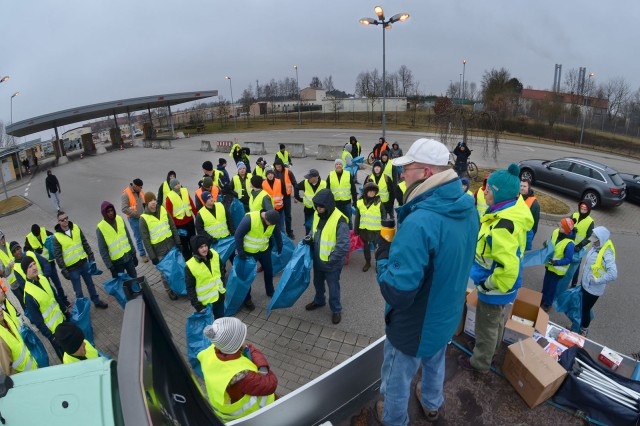 """ANSBACH, Germany -- A group of volunteers receive information about the city of Ansbach's official """"Cleanup Day"""" known locally as Ansbach Saub(ä)er from Walt Mattil, Chief, USAG Ansbach Directorate or Public Works (DPW) in the parking lot at the entrance of Katterbach Kaserne, March 17, 2018. USAG Ansbach DPW supplied U.S. participants with their reflective vests, gloves, trash bags, and trash-grabbing tools and coordinated groups of Soldier with nearby areas designated for clean-up. The city of Ansbach holds the city-wide cleanup annually. During this year's Saub(ä)er, more than 200 Soldiers, family members and U.S. civilians spent the Saturday morning walking along the roads that surround the kasernes to pick up litter. Though the morning was cold, grey and dismal and the hour was early, Soldiers and Civilians were in good spirits and made the cleanup march a light-hearted hike, jogging, taking selfies and socializing as they scoured the roadways and parks in the towns they walked through. USAG Ansbach Directorate of Public Works (DPW) supplied the U.S. participants with the reflective safety vests, gloves, trash bags and trash grabbing tool and coordinated groups of Soldiers to clean up designated nearby areas."""