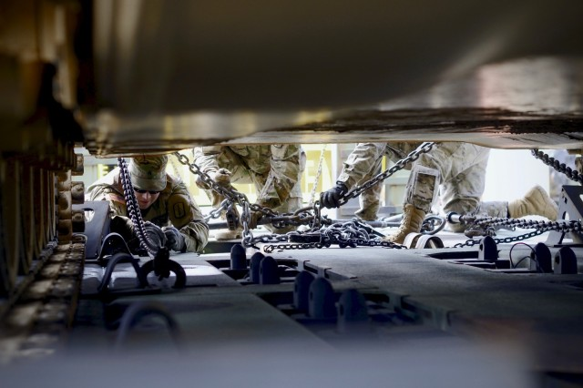 North Carolina National Guard soldiers with the 1452nd Heavy Equipment Transportation Company, 113th Sustainment Brigade, adjust chains securing a M1A1 Abrams tank to a M1000 trailer at Fort Bragg, North Carolina, on Mar. 17, 2018. The trailer will be pulled by a M1070 Heavy Equipment Transporter to Fort Pickett, Virginia, to be used by the 30th Armored Brigade Combat Team during gunnery, in preparation for the 30th ABCT upcoming eXportable Combat Training Capability (XCTC) training.