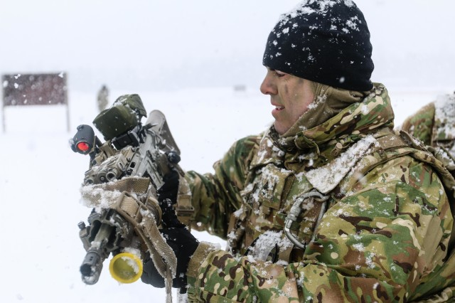 Army Staff Sgt. Jason Shick, a chemical, biological, radiological and nuclear specialist with the 82nd Brigade Engineer Battalion, examines a Danish 5000 Colt C8 IUR carbine during a multinational weapons training session with Danish soldiers as part of a rapid response readiness exercise in support of the Atlantic Resolve mission in Tapa, Estonia, March 10, 2018.