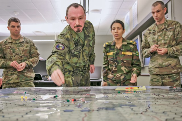 "Czech Army Major Jiri ""Jorge"" Pazdera (center) moves markers on the map of ""Landpower,"" a board game simulation exercise as Maj. Adam Keller (left), Bangladeshi Maj. Tasnuva Tabassum and Maj. Zachary Labrayere (right) watch at The U.S. Army Command and Staff College on Fort Leavenworth, Kan., March 9. Landpower underwent pilot-testing to determine if it is a suitable replacement for college's current computer based simulations that take much longer to teach."