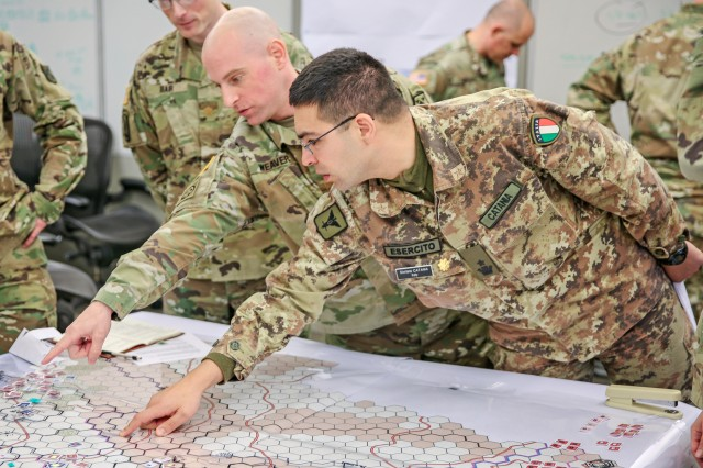 "Italian Army Maj. Stefano Catania (right) and U.S. Army Maj. Keith Weaver discuss potential locations of their troops during a game of ""Landpower"" as U.S. Army Maj. Colin Bair (back left) observes at the U.S. Army Command and Staff College, Fort Leavenworth, Kan. Landpower, a hex and map-based board game, was tested March 9-15 to evaluate its potential to replace or augment the current college's computer-based simulation that takes more time and manpower to operate."
