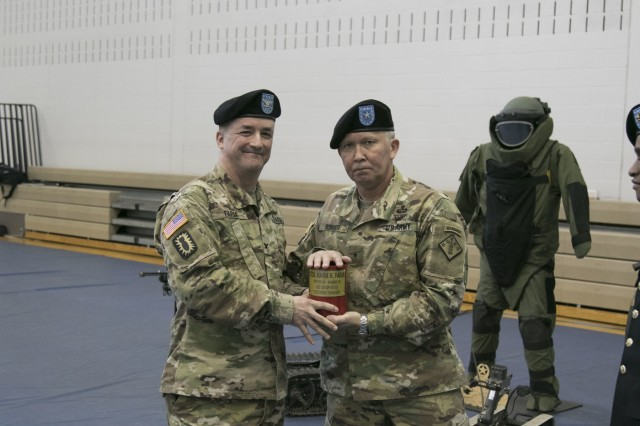 Col. Mark R. Faria, left and former commander of the 52nd Ordnance Group (EOD), 20th Chemical, Biological, Radiological, Nuclear and high-yield Explosive Command, receives the last shell fired during honors from Brig. Gen. James E. Bonner, commanding general of the 20th CBRNE Cmd. during a change of command ceremony in Sabo Physical Fitness Center on Fort Campbell, Ky., Mar. 14, 2018. Bonner had deferred the honors to Faria in recognition for Faria's time in command of the group as this ceremony was when Faria relinquished command as this ceremony was when Faria relinquished command.