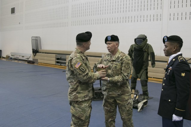 Col. Mark R. Faria, left and former commander of the 52nd Ordnance Group (EOD), 20th Chemical, Biological, Radiological, Nuclear and high-yield Explosive Command,acceptst the shell fired during from  Brig. Gen. James E. Bonner, commanding general of the 20th CBRNE Cmd., during a change of command ceremony in Sabo Physical Fitness Center on Fort Campbell, Ky., Mar. 14, 2018. Bonner had deferred the honors to Faria in recognition of Faria's time in command of the group as this ceremony was whenCol. Mark R. Faria, left and former commander of the 52nd Ordnance Group (EOD), 20th Chemical, Biological, Radiological, Nuclear and high-yield Explosive Command, receives the last shell fired during honors from Brig. Gen. James E. Bonner, commanding general of the 20th CBRNE Cmd. during a change of command ceremony in Sabo Physical Fitness Center on Fort Campbell, Ky., Mar. 14, 2018. Bonner had deferred the honors to Faria in recognition for Faria's time in command of the group. (U.S. Army photo by Staff Sgt. Adam Hinman, 52nd Ordnance Group (Explosive Ordnance Disposal), 20th Chemical, Biological, Radiological, Nuclear and high-yield Explosives Command, Public Affairs) Faria relinquished command.