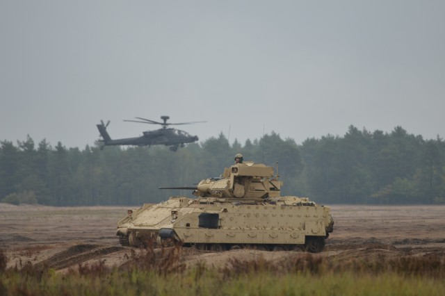 Apache helicopters from the 1st Attack Reconnaissance Battalion, 501st Aviation Regiment, Combat Aviation Brigade, regroup at a new battle position with Bradley Fighting Vehicles and Abrams tanks from the 5th Squadron, 4th Cavalry Regiment, 2nd Armored Brigade Combat Team, during a readiness demonstration, Presidenski Range, Trzebian, Poland, Sep. 25, 2017. U.S. Army Europe conducts frequent exercises with European and NATO allies to ensure security and deter Russian aggression.