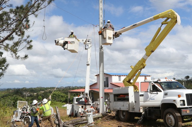 """Despite the rugged terrain, power workers with the U.S. Army Corps of Engineers (USACE) contractor """"Power Secure"""" reconnect power lines near the town of Lares, Puerto Rico, Jan. 24, 2018. An estimated 80 percent of the power grid in Puerto Rico was destroyed by Hurricane Maria, in September 2017. FEMA assigned the United States Army Corps of Engineers to the lead the federal effort to repair the hurricane-damaged electrical power grid in support of the Government of Puerto Rico."""