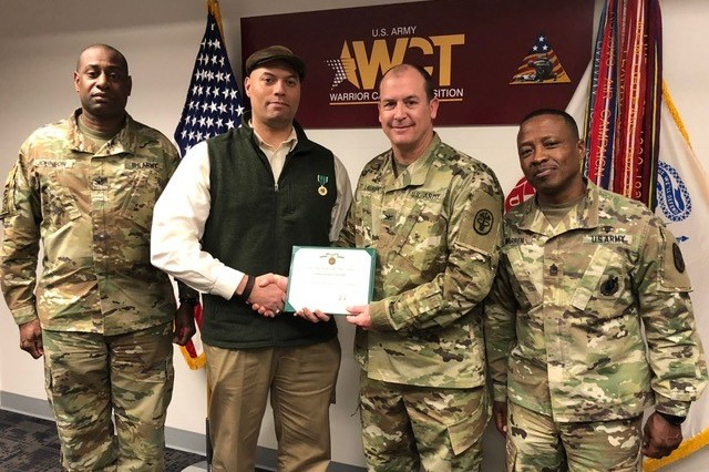 U.S. Army Reserve Capt. Brandon Henderson-Adams (second from left) poses for a picture with (left to right) Col. Terrance Johnson, Col. Matthew St Laurent, and Sgt. Maj. Darryl Warren as he receives the Commander's Award for Civilian Service on March 15, 2018.