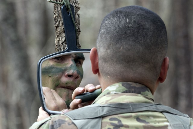 Staff Sgt. Giovanti Lugo, an infantryman and drill sergeant with the 193rd Infantry Brigade applies face paint during EIB testing March 20. After a grueling first day of testing, 161 infantrymen began the patrol lanes phase of testing March 20.