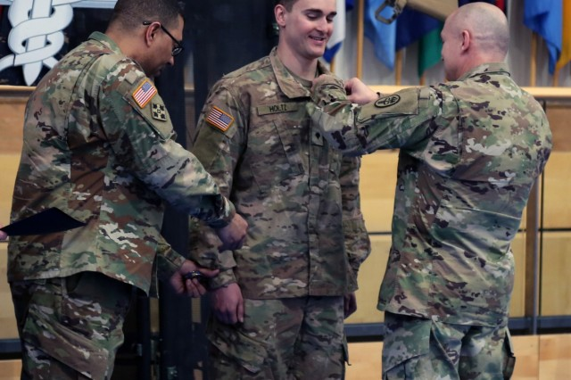 Command Sgt. Maj. Joseph Cecil (right), Regional Health Command-Europe command sergeant major, pins the Expert Field Medical Badge onto Spc. Matthew Holtz (center), medic with 1st Battalion-503rd Infantry Regiment, 173rd Airborne Brigade as Col. Jordan Henderson (left), 212th Combat Support Hospital commander, hands Holtz a command challenge coin during the ceremony for the U.S. Army Europe Spring 2018 Expert Field Medical Badge, March 21, at Tower Barracks Physical Fitness Center, Grafenwoehr, Germany. Holtz was recognized as the honor graduate.