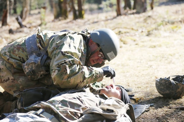 Staff Sgt. Matthew Adams, healthcare sergeant from Regional Health Comamnd-Europe, checks a patient for Pupils Equal and Reactive to Light on a simulated casualty, during U.S. Army Europe's Spring 2018 Expert Field Medics Badge testing, March 20, in Grafenwoehr, Germany.