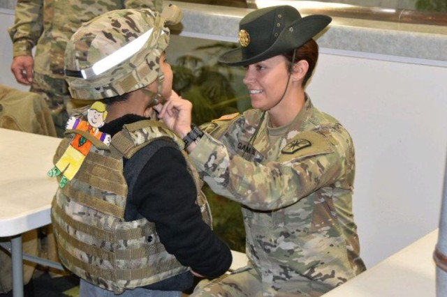 Staff Sgt. Emily Gamble, 14th Military Police Brigade drill sergeant, shows 6-year-old Noah Molitor of Overland Park, Kansas, how to use protective gear during Army Day at the St. Louis Science Center, Friday.