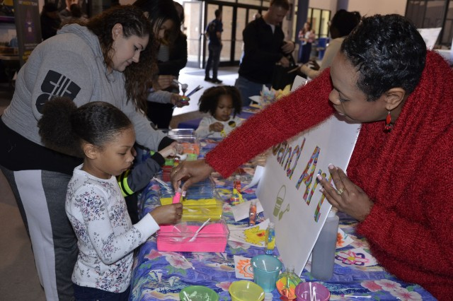 Sharon Brown, Program Operations Specialist, Child Youth Service helps Kennedi Demons with a sand art project at the 193rd Infantry Brigade Connecting Day/Informational Day March 10. Community organizations fill the Solomon Center with fun activities and information for family resources on and off post.