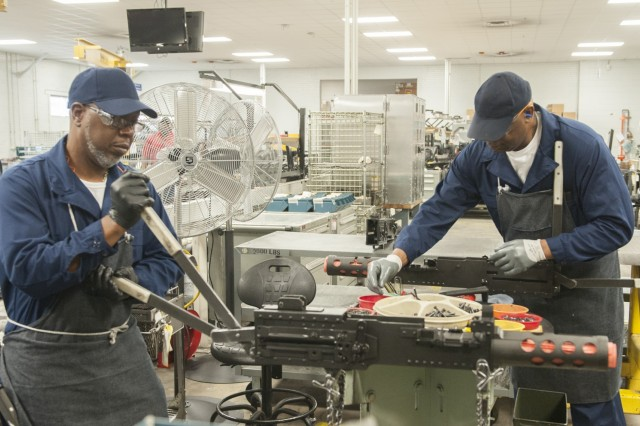 Clarence Street, left, and Clay Usher install latches and the top cover on M2A1 machine guns in Anniston Army Depot's Small Arms Repair Facility.