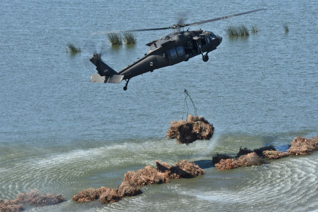 Louisiana National Guardsmen from 1st Assault Helicopter Battalion, 244th Aviation Regiment drop bundles of recycled Christmas trees from a UH-60 Black Hawk into Bayou Sauvage National Wildlife Refuge in New Orleans East to help combat coastal erosion, March 14, 2018. The project has re-established hundreds of acres of marshland in the Bayou Sauvage NWR over the last 23 years. This year, the LANG and the U.S. Fish and Wildlife Service emplaced approximately 8,000 trees.
