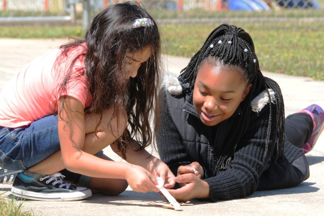 Sophia Castillo, second grader, and Moriah Wesley, sixth grader, test out their catapult as they launch marshmallows.