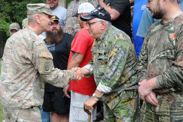 Lt. Col. Scott Wile, Directorate of Public Safety director and provost marshal, presents wounded warriors with a coin during the Wounded Warrior Fall Hunt closing ceremony on West Beach at Lake Tholocco last year.