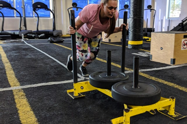 Jenni Lowell, military spouse, works on the sled push during the functional fitness competition at Fort Drum on March 22.