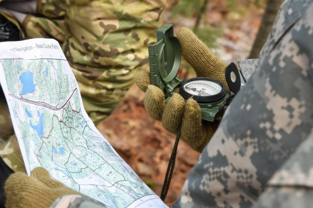 A Soldier with the U.S. Army Natick Soldier Research Development and Engineering Center's Headquarters Research and Development Detachment looks at a map and compass during land navigation training conducted at Fort Devens, Massachusetts in February 2018.