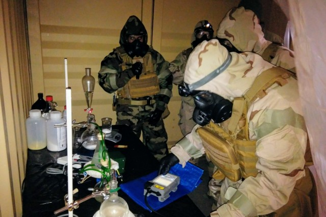 Airmen from 48th Civil Engineer Squadron, 48th Mission Support Group, capture sensitive information in a clandestine lab during a Chemical, Biological, Radiation and Nuclear  training exercise coordinated by Defense Threat Reduction Agency Europe at Stanford Training Area, Norfolk, England, March 8, 2018. (Courtesy Photo)