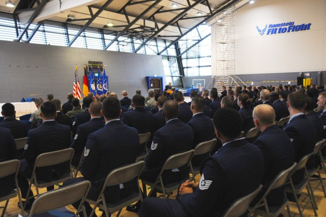 U.S. Airmen listen to opening remarks at the U.S. Air Forces in Europe Kislinger NCO academy graduation ceremony at Ramstein Air Base, Germany, March 23, 2018.
