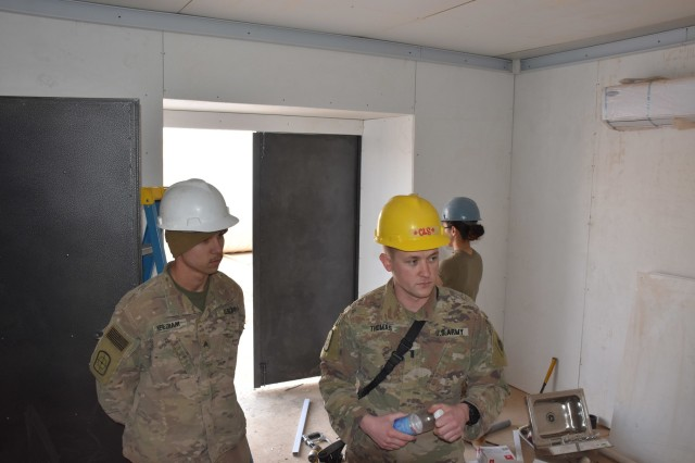 Sgt. Eric Needham of McAlester, Okla., and 1st Lt. Jonathan Thomas of Bixby, Okla., discuss the challenges the 2120th Engineers faced while building the Troop Medical Clinic in Iraq.