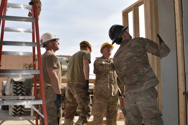 Spc. Austin Michael (right) of Piedmont, Okla., checks the square of the new emergency entrance doorway on the Troop Medical Clinic. The TMC was built in Iraq by the 2120th Engineer Company, 458th Engineer Battalion, 35th Engineer Brigade, Task Force Spartan.