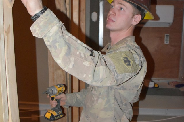 Spc. Steven Ward of Oklahoma City puts his civilian skills as a subcontractor to use as he frames out a doorway for a new office in the Iraqi customs building.  Ward is a soldier with the 2120th Engineer Company, 458th Engineer Battalion, 35th Engineer Brigade, Task Force Spartan.