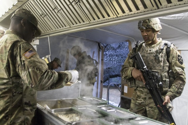 A Soldier with 1-2 Stryker Brigade Combat Team serves breakfast March 22, 2018, at Joint Base Lewis-McChord, Washington, during the Department of the Army Philip A. Connelly Competition. Evaluators from the Department of the Army inspected the team's field feeding site, situated at Training Area 12 on JBLM, questioning members of the team and examining the team's operational implementation of regulations covering food service. (U.S. Army photo by Staff Sgt. Samuel Northrup)