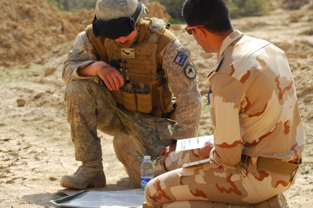 A New Zealand army instructor (left) explains a battlefield training scenario to an Iraqi army student during the Iraqi forward air control course live-fire training exercise March 8, 2018 in Besmaya, Iraq.