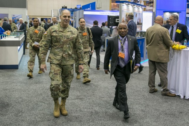 Army Materiel Command commander Gen. Gus Perna is escorted by Jesse Barber, the commands' ombudsman, as they visit with defense contractors exhibiting at AUSA's 2018 Global Force Symposium and Exhibition in Huntsville, Ala., March 26, 2018.