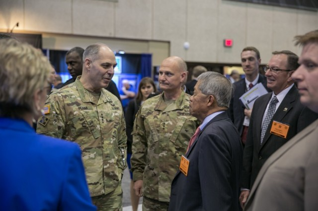 The Army Materiel Command's Gen. Gus Perna and Lt. Gen. Ed Daly discuss industry partnerships with defense company representatives during their visit to the exhibit hall at AUSA's 2018 Global Force Symposium and Exhibition in Huntsville, Ala., March 26, 2018.