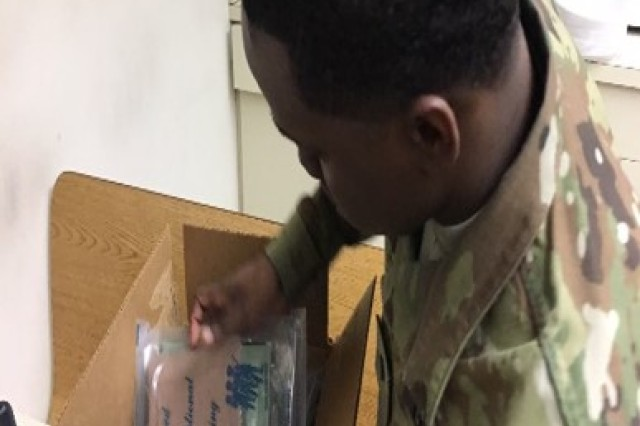 SPC Jordan Murray inspects the ration packaging for defects.