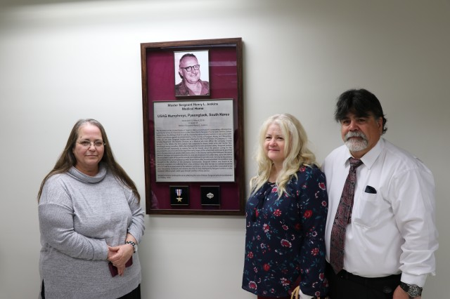 Master Sgt. Henry L. Jenkins' daughter, Linda (left), son Michael and daughter-in-law, Trina pose in front of the Bronze Star plaque in the foyer of the memorialized Patient Center Medical Home on U.S. Army Garrison Humphreys.