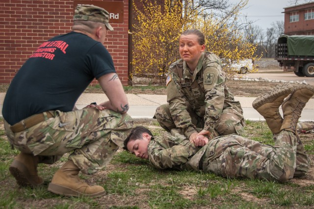 Pfc. Arianna Hintermeister, Co. C, 701st Military Police Battalion, demonstrates proficiency in unarmed self-defense holds and take downs to Staff Sgt. Daniel Lagant, Non-Lethal Weapons instructor, as part of corrections and detention specialist training March 23. The Advanced Individual Training Soldiers are sprayed with oleoresin capsicum, or OC, before moving through four stations where instructors say they are forced to trust themselves and their training in order to pass.