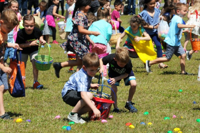 Children race to collect eggs during the Easter egg hunt at Children's Fest at the festival fields March 24.