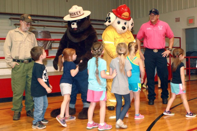 Children from Frink-Chambers School in McAlester, Okla., greet Smokey and Sparky from the Oklahoma Forestry Service following a Fire Prevention Week assembly at the school, Oct. 17, 2016. The McAlester Army Ammunition Plant Fire and Emergency Services team partnered with the McAlester Fire Department and Oklahoma Forestry Service to teach the students about fire safety.