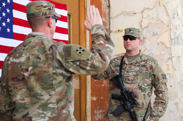 Maj. Patrick Devine (left), chaplain, Train, Advice, Assist Command-South and 2nd Infantry Brigade Combat Team, 4th Infantry Division, officiates the re-enlistment ceremony for Staff Sgt. Marcus P. Levering, religious affairs noncommissioned officer, TAAC-South and 2nd IBCT, 4th Inf. Div., March 17, 2018, in Kandahar, Afghanistan.