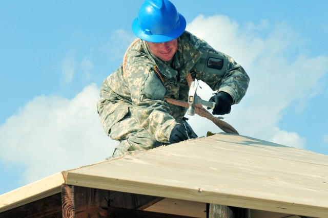 A U.S. Army Soldier assigned to the 859th Engineer Company from the Mississippi Army National Guard secures some of the last boards of the roof section of the gazebo. These Soldiers spent their annual training at the Joint Multinational Readiness Center's Hohenfels Training Area, Hohenfels, Germany, building several construction projects March 11 -- 31. For many of the younger Soldiers this is the first time building anything of this scale since their initial military occupational skill training.