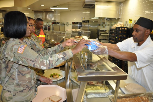 A Soldier receives her lunch from a dining facility employee March 22, 2018, at Fort Lee, Virginia. The Mission and Installation Contracting Command-Fort Lee office administers the full-food service contract that served more than 5 million meals to warfighters on Fort Lee in fiscal 2017.