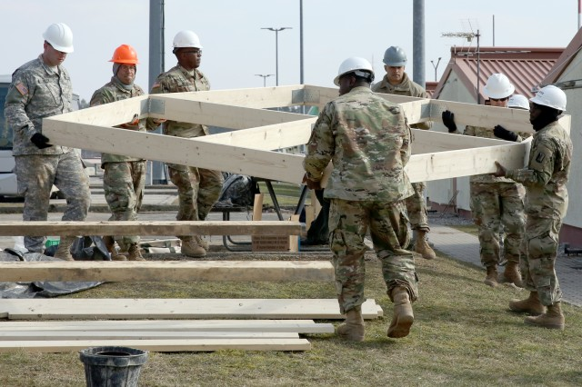 U.S. Army Soldiers assigned to the 859th Engineer Company from the Mississippi Army National Guard move the roof section that was just assembled to be stained. These Soldiers spent their annual training at the Joint Multinational Readiness Center's Hohenfels Training Area, Hohenfels, Germany, building several construction projects March 11 -- 31. For many of the younger Soldiers this is the first time building anything of this scale since their initial military occupational skill training.