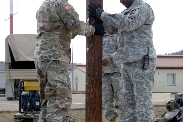 U.S. Army Soldiers assigned to the 859th Engineer Company from the Mississippi Army National Guard install a vertical support beam onto the concrete slab, which will soon start to resemble a gazebo. These Soldiers spent their annual training at the Joint Multinational Readiness Center's Hohenfels Training Area, Hohenfels, Germany, building several construction projects March 11 -- 31. For many of the younger Soldiers this is the first time building anything of this scale since their initial military occupational skill training.
