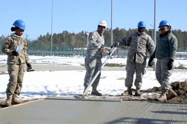 A senior member of the 859th Engineer Company, Mississippi Army National Guard, instructs other Soldiers with proper techniques of smoothing out the concrete, which will soon resemble a finished concrete slab. The slab will become the concrete foundation under the gazebo. These Soldiers spent their annual training at the Joint Multinational Readiness Center's Hohenfels Training Area, Hohenfels, Germany, building several construction projects March 11 -- 31. For many of the younger Soldiers this is the first time working with concrete since their initial military occupational skill training.