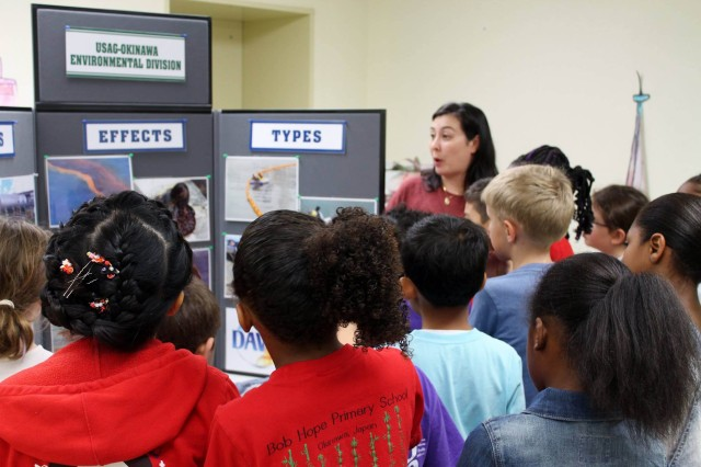"Brandy Hawley, Environmental Chief, participates in STEM Day at Kadena Bob Hope Primary School, April 21, 2017. Eager students listen to a presentation about oil spills and its impact on animals. They also experienced hands-on clean-up of animals at the ""wildlife rehabilitation center."""