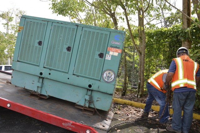 Contract workers for the U.S. Army Corps of Engineers install a temporary emergency power generator at a school in Puerto Rico, Feb. 26, 2018.