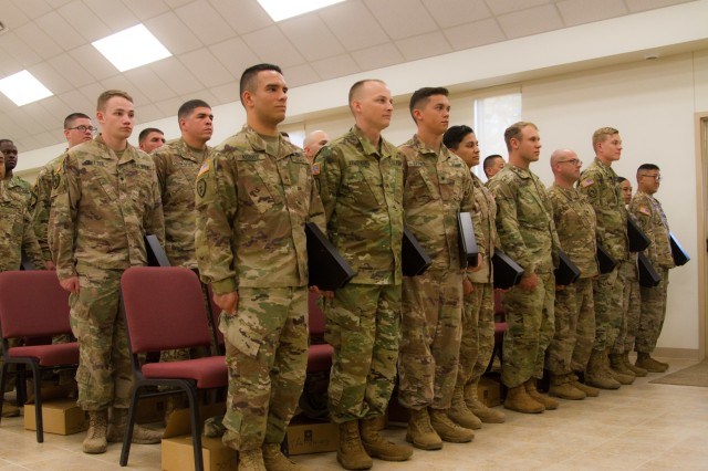 US Army Soldiers from the 319th Expeditionary Signal Battalion, 505th Signal Brigade, 335th Signal Command [Theater], stand at attention after receiving awards for a job well done while overseas at North Fort Hood, Texas, on March 24, 2018. This reserve battalion walked away from their civilian lives to enhance and train American Allies in cutting edge cyber security and warfare techniques all across the Horn of Africa, strengthening communications between the US and its African Allies. (US Army photo taken by Spc. Nicholas Vidro, 7th Mobile Public Affairs Detachment.)