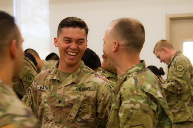 """US Army Spc. Alexander Bastilo, a multichannel transmission systems operator-maintainer with company B, 319th Expeditionary Signal Battalion, 505th Signal Brigade, 335th Signal Command [Theater], laughs one last time before departing a """"welcome home"""" ceremony held on behalf of the battalion at North Fort Hood, Texas, on March 24, 2018. This full-time student transferring to Pennsylvania State University this upcoming spring just completed a 12 month deployment to the Horn of Africa along with fellow Soldiers of the 319 ESB. Together they enhanced communications with and for America's African Allies. (US Army photo taken by Spc. Nicholas Vidro, 7th Mobile Public Affairs Detachment.)"""