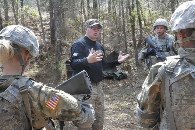 Staff Sgt. Christopher Penley, a combatives instructor, leads an after-action review following the training scenario.