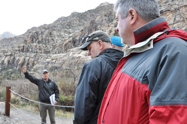 Keith Kelson, engineering geologist with the U.S. Army Corps of Engineers Sacramento District, background left, discusses how clues from pre-historic and historic floods can help predict future flooding events with other U.S. Army Corps of Engineers geologists during an exercise March 15 at the Red Rock Canyon National Conservation Area near Las Vegas.