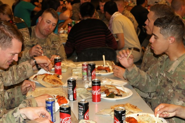 Afghan contractors and Soldiers of Train, Advise, and Assist Command South, comprised of the 40th Infantry Division, California National Guard, and the 2nd Infantry Brigade Combat Team, 4th Infantry Division, eat traditional Afghan food during a Nauruz celebration on Kandahar Airfield, Afghanistan, March 21, 2018.  The Afghan contractors, who planned and hosted the celebration, invited the TAAC-South Soldiers to experience the Afghan New Year. (U.S. Army photo by Maj. Richard Barker/TAAC-South Public Affairs)