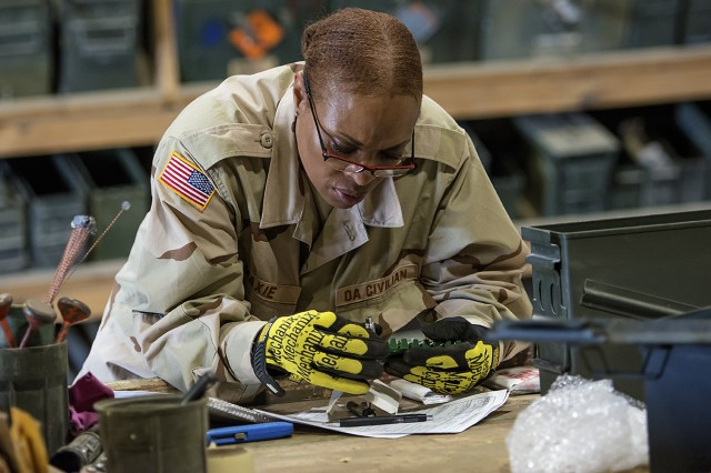 Tameka Maxie, quality assurance specialist, ammunition surveillance, Army Field Support Battalion-Afghanistan examines small arms ammunition during a periodic inspection at Bagram Airfield, Afghanistan, March 31. (U.S. Army Photo by Justin Graff, 401st AFSB Public Affairs)